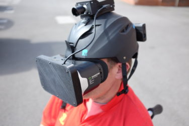A man in a red football shirt wearing a ski helmet attached to a VR headset and small webcam